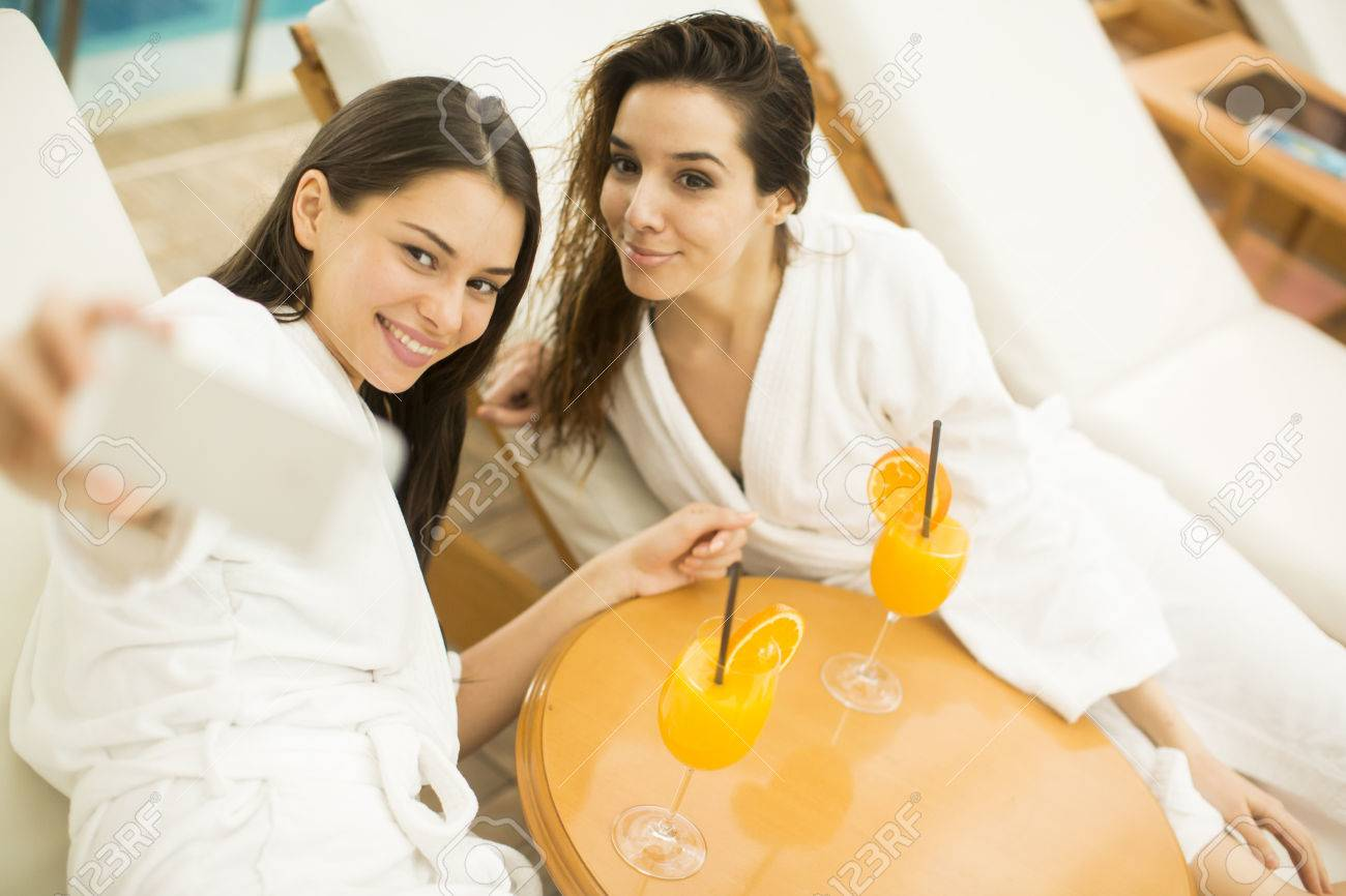 two young ladies clothed bathrobe lying down on deckchairs, and
