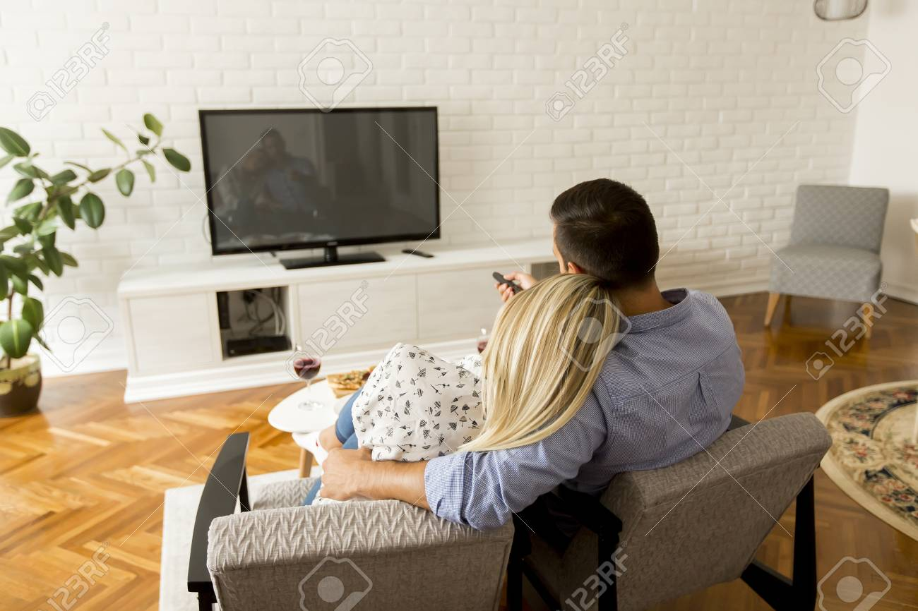 Rear view of couple watching television in living room - 110294818