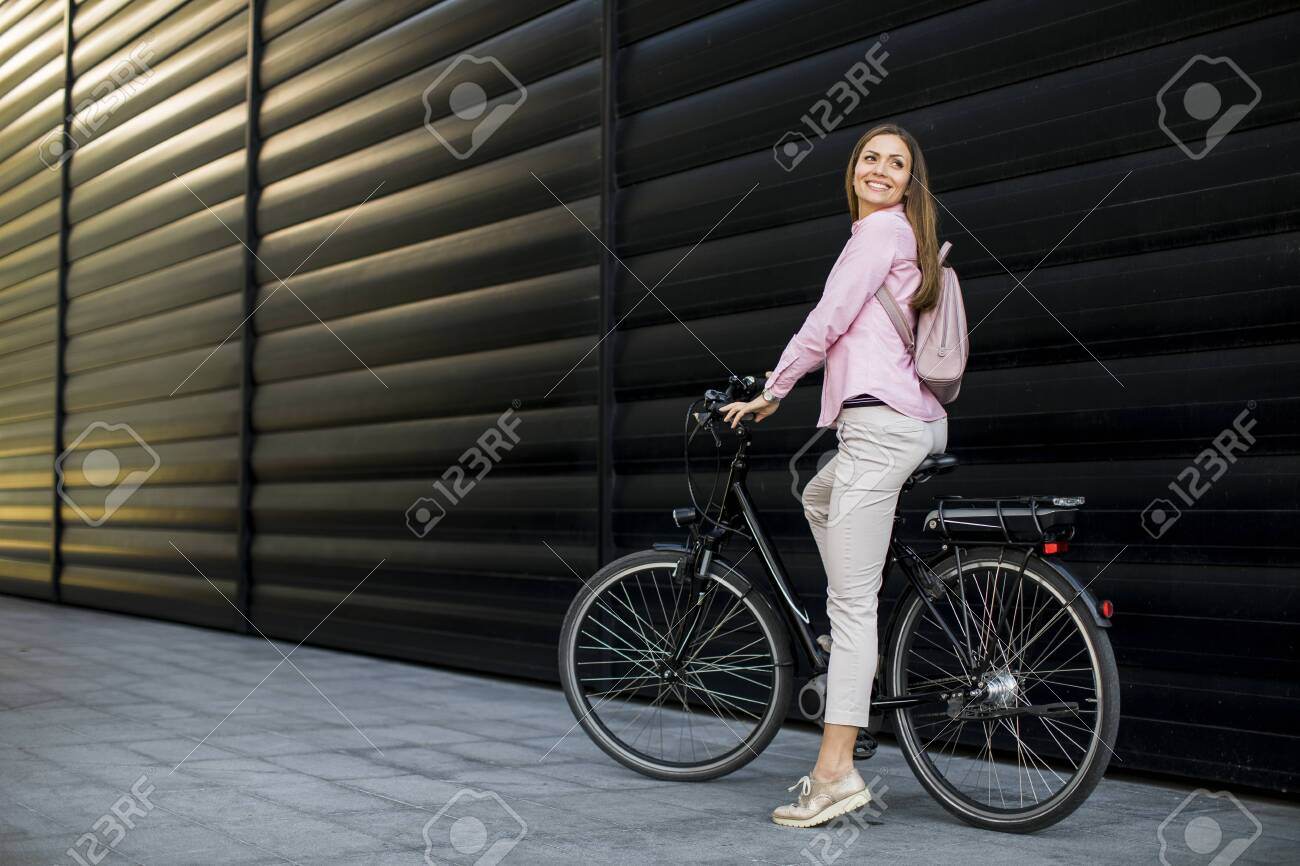 Pretty young woman with modern city electric e-bike as clean sustainable urban transportation - 134387959