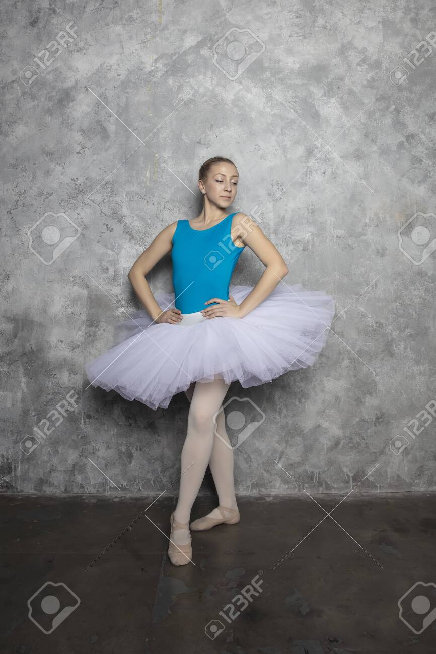 Pretty young ballerina dancer dancing classical ballet against rustic wall - 143194366