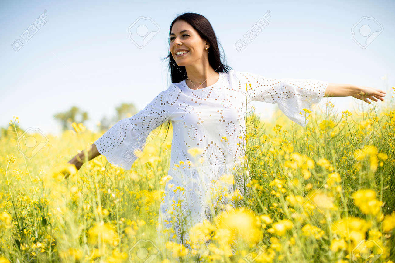 Pretty young woman in the rapeseed field - 169026638