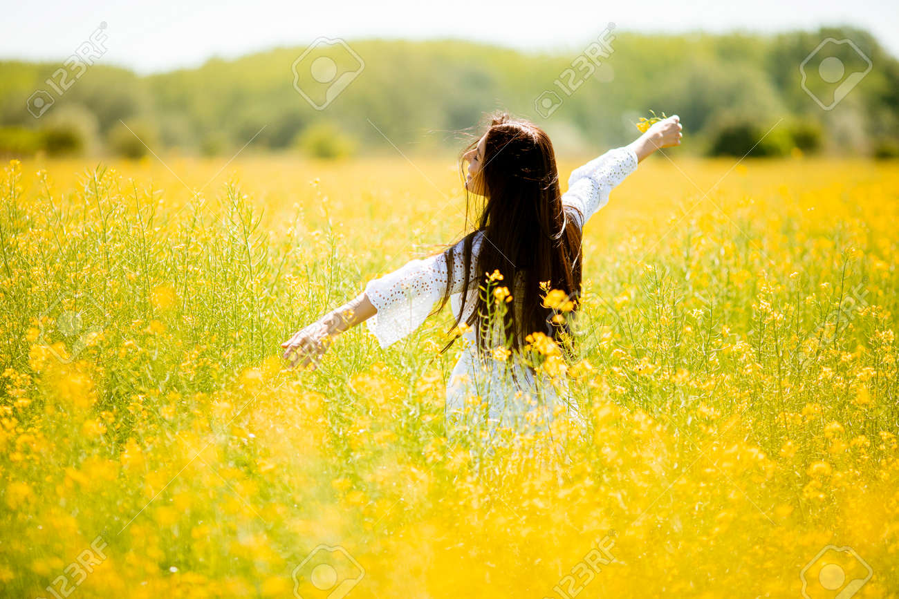 Pretty young woman in the rapeseed field - 169026727