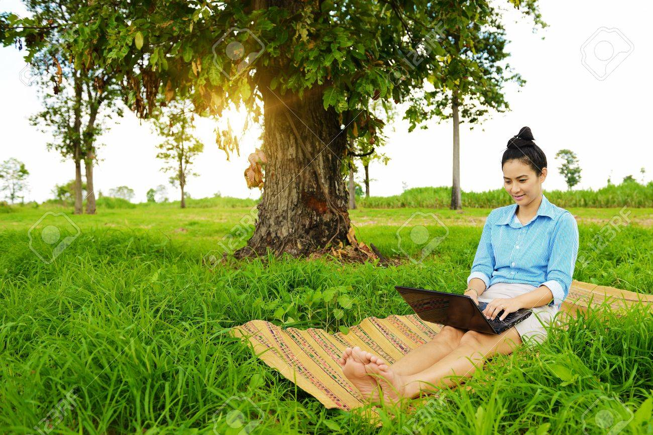 Business woman using laptop in the field - 22159229