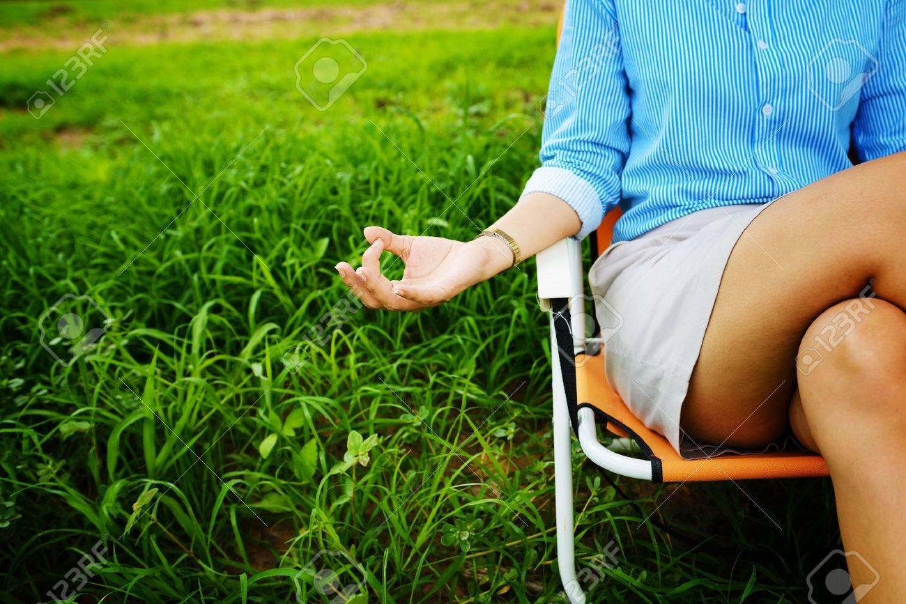 Business woman meditating and making yoga at green field - 22160196