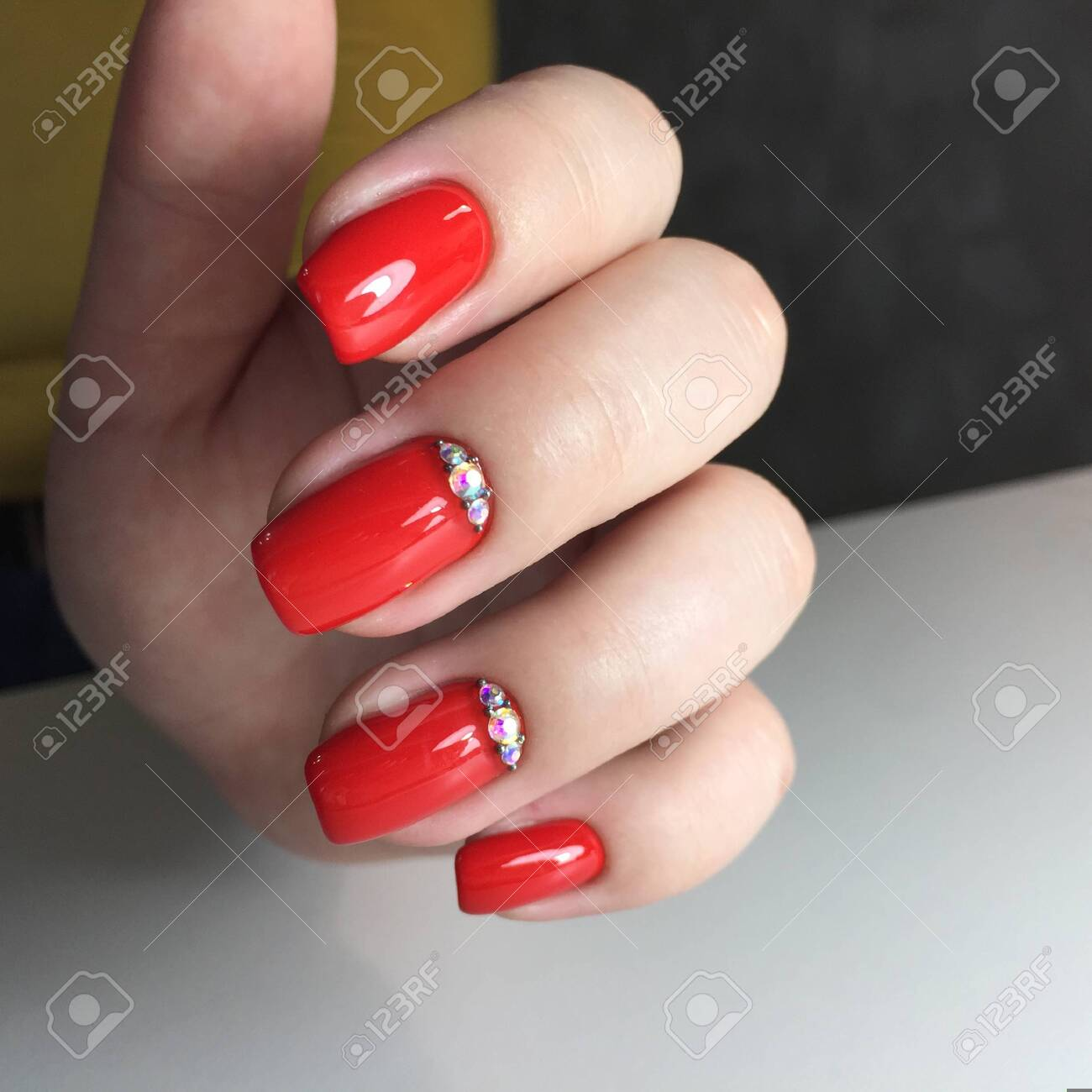 Closeup photo of a beautiful female hands with red nail.Beautiful female hands with red manicure on a dark background - 143083362