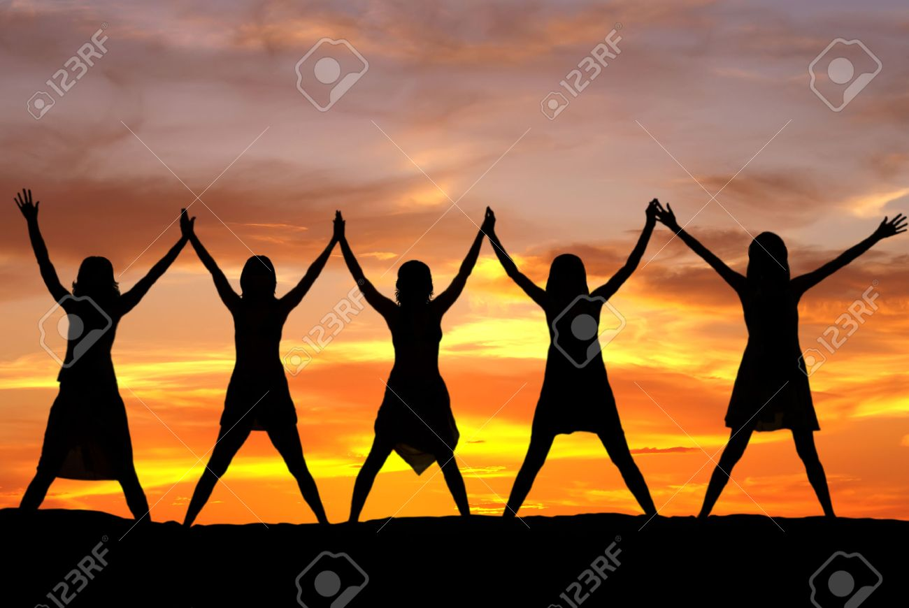 Happy celebrating women at sunset or sunrise standing elated with arms raised up above their heads - 34517527