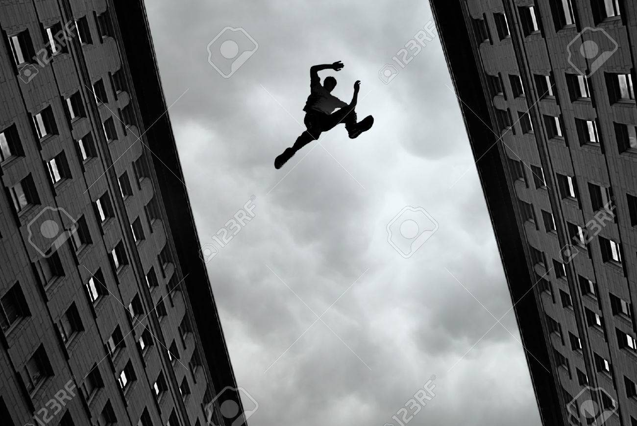 man jumping over building roof against gray sky background stock
