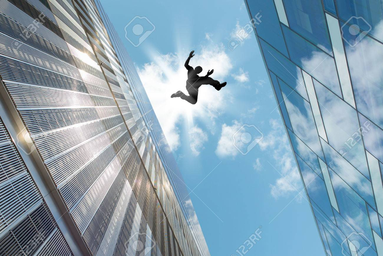 man jumping over building roof against blue sky background stock