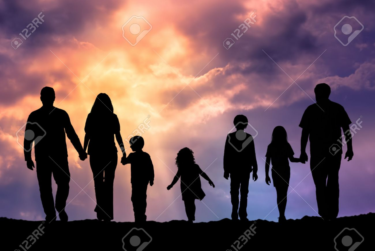 Silhouette of a family comprising a father, mother and children walking into the sunset - 41429331