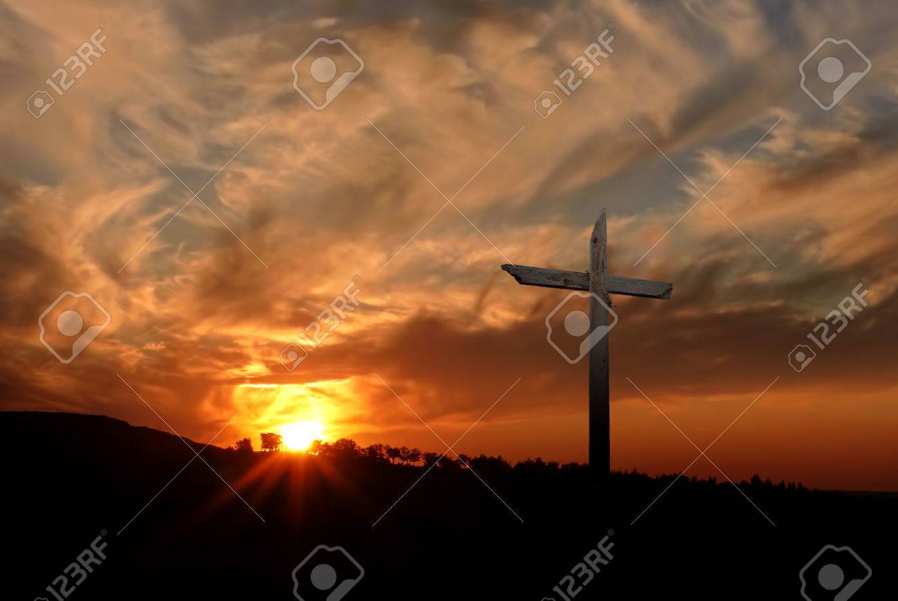 Silhouette of Christian cross at sunrise or sunset with light rays - 53518318