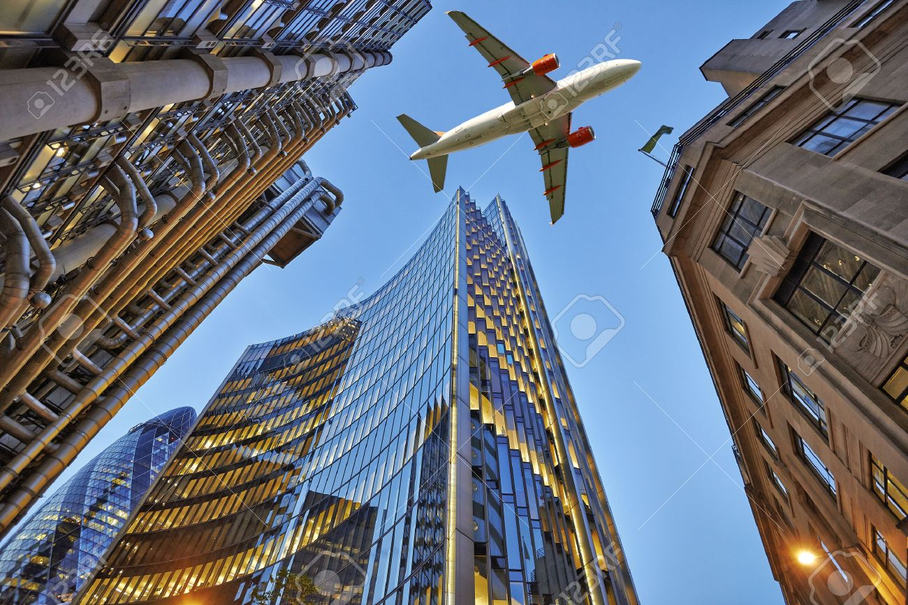 A jet plane flying low over Three different kind of architecture exterior trade with office buildings. Evening view at bottom skyscrapers. Standard-Bild - 39280784