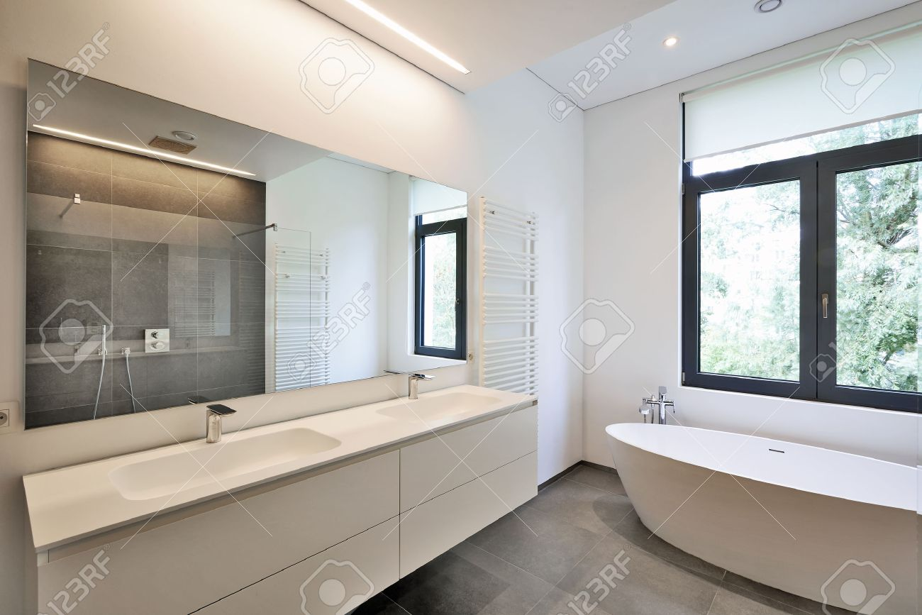 Bathtub in corian, Faucet and shower in tiled bathroom with windows towards garden Standard-Bild - 42832904