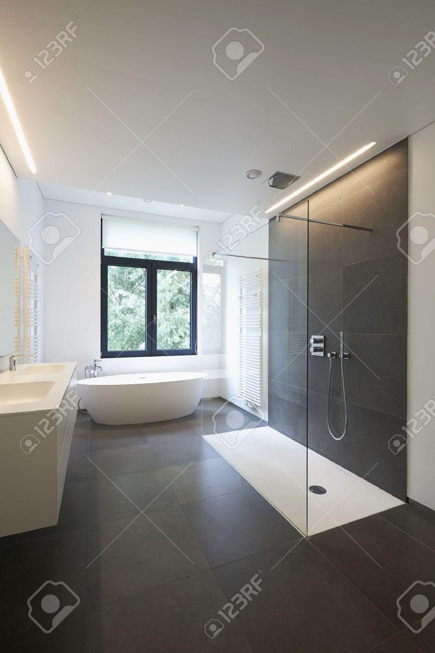 Badkar i corian, kran och dusch i helkaklat badrum med fönster mot ...