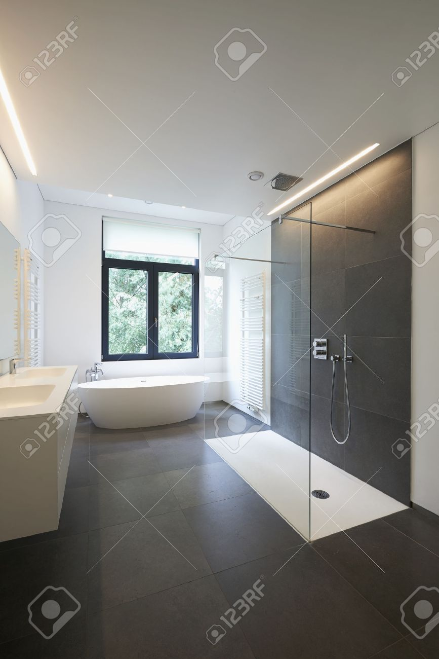 Bathtub in corian, Faucet and shower in tiled bathroom with windows towards garden Standard-Bild - 42832908