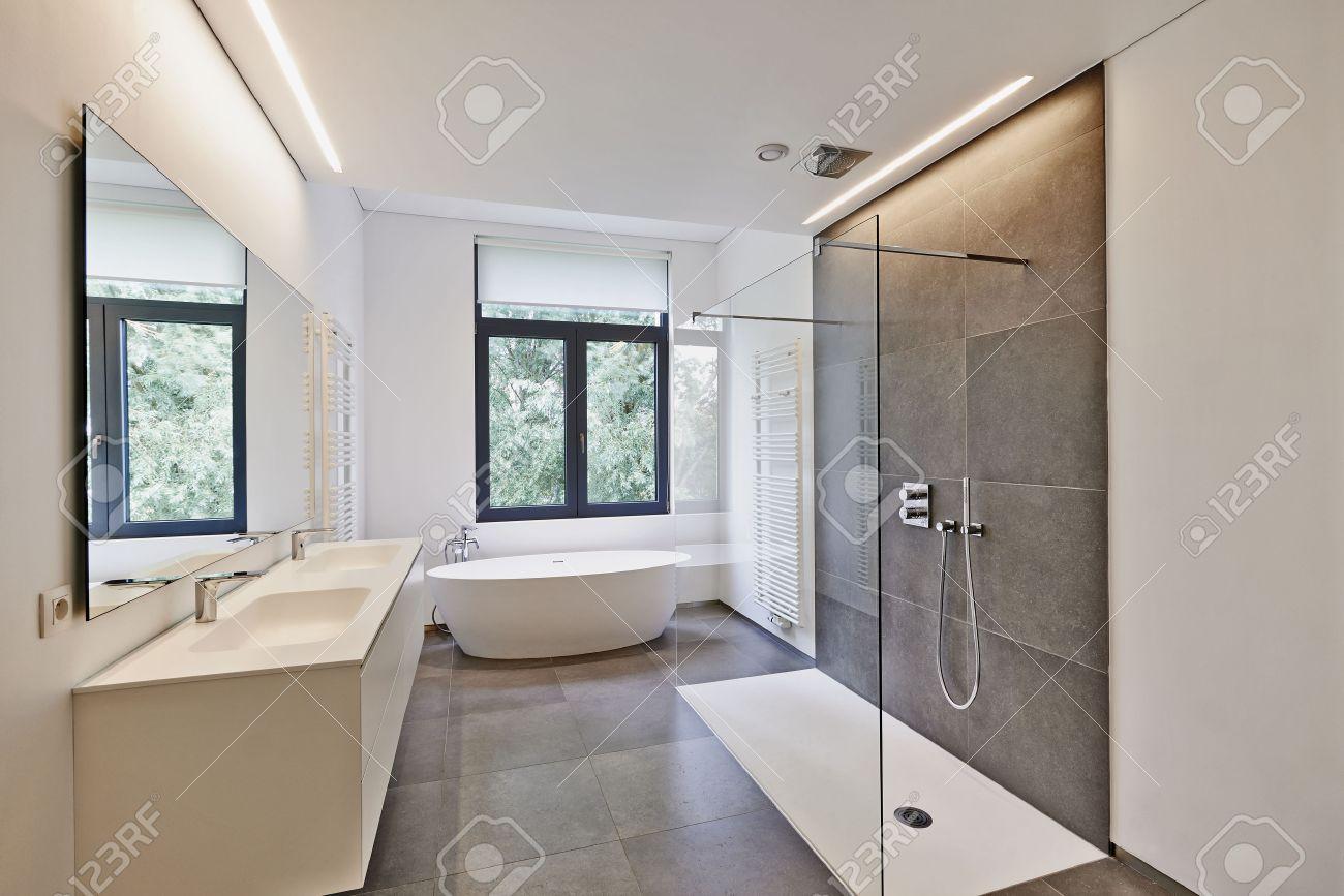 Badewanne Aus Corian, Wasserhahn Und Dusche Im Gefliesten Bad Mit Fenster  In Richtung Garten Lizenzfreie