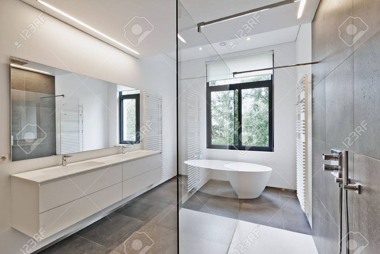 Bathtub in corian, Faucet and shower in tiled bathroom with windows towards garden Standard-Bild - 42832912