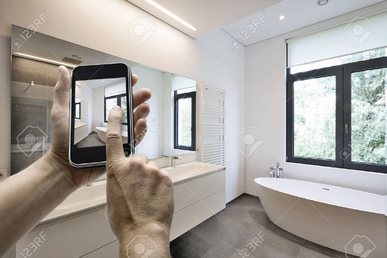 Mobile device with man hands taking picture in  tiled bathroom with windows towards garden Standard-Bild - 45161853