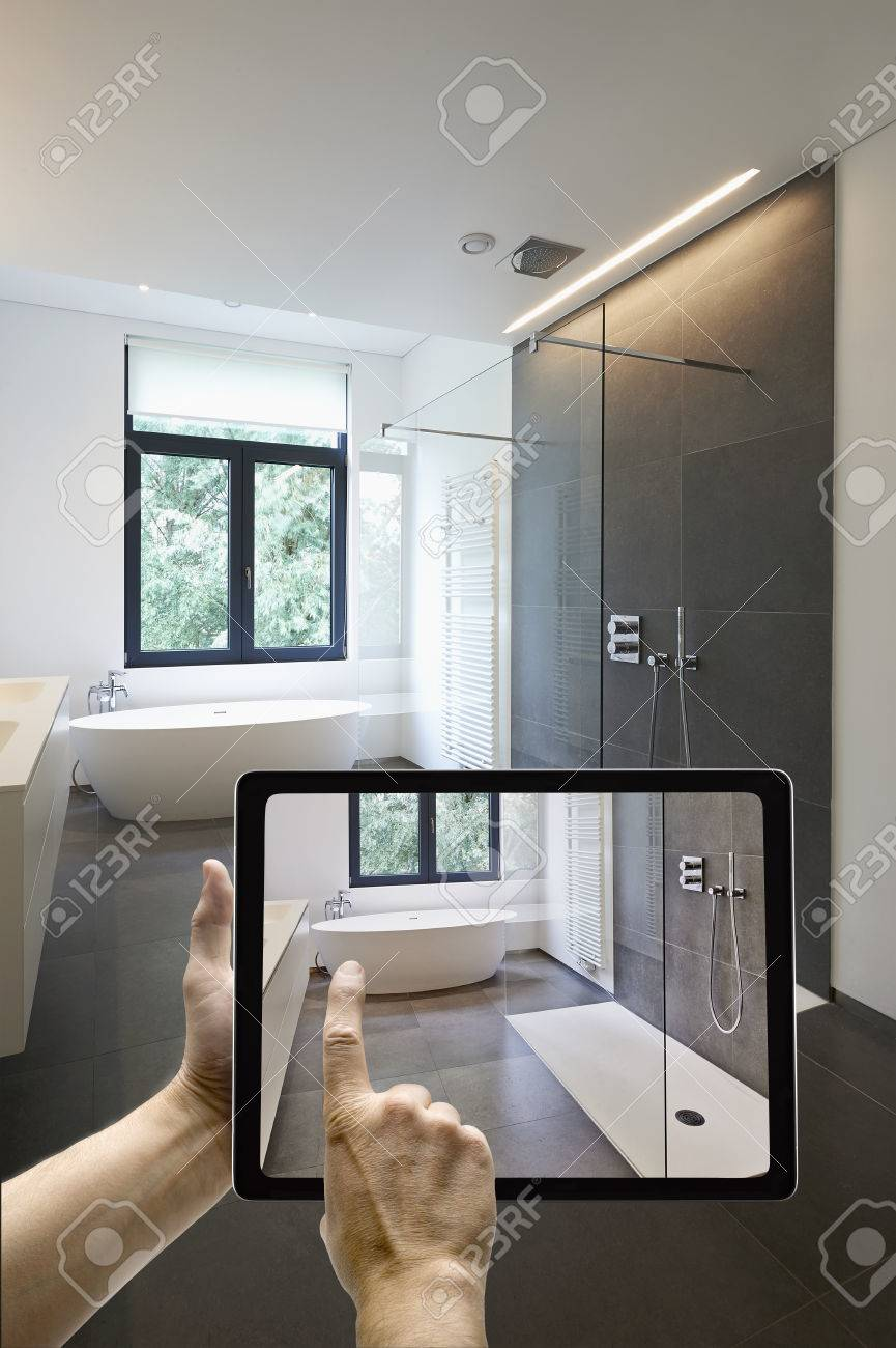 Mobile device with man hands taking picture in  tiled bathroom with windows towards garden Standard-Bild - 52472155