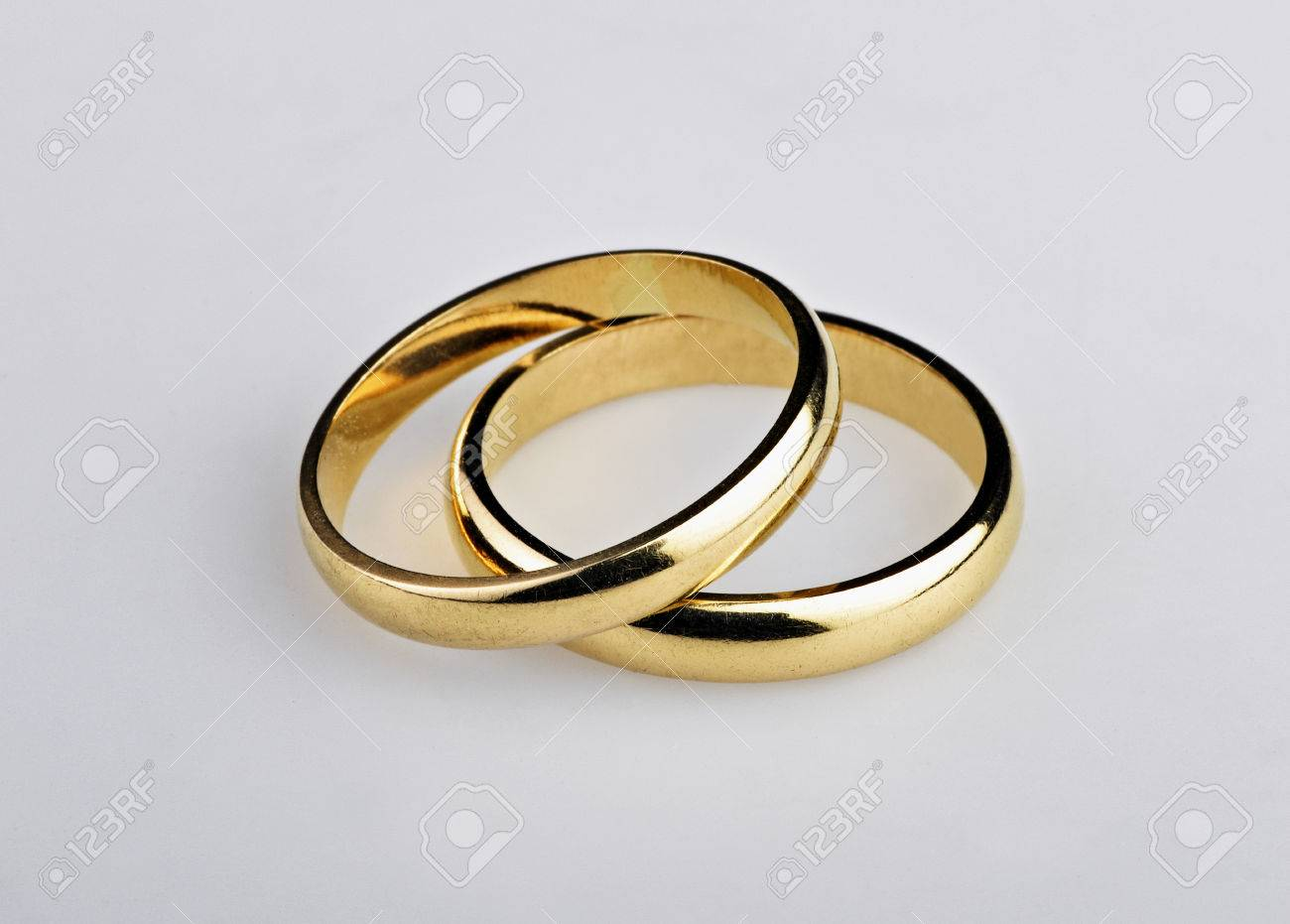 stock photo two well used golden wedding rings on gray background - Used Wedding Rings