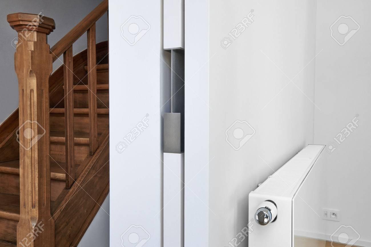 Standard Bild   Weiße Heizkörper An Der Wand Mit Tür Mit Holzboden In Einer  Wohnung Schiebe