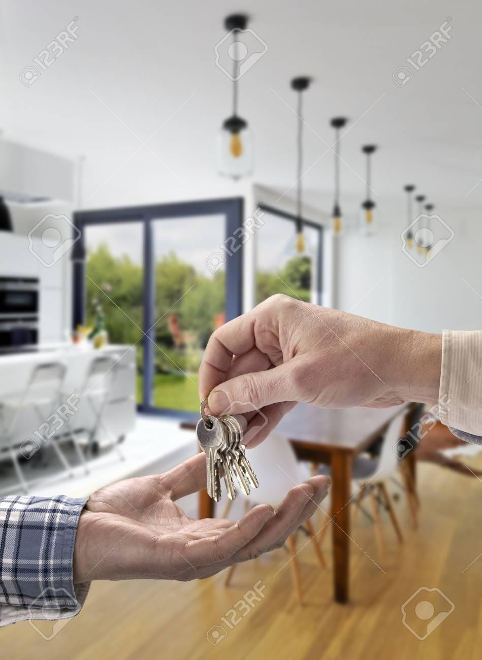 Clé de la maison à l\'acheteur dans un salon de luxe avec vue sur le jardin