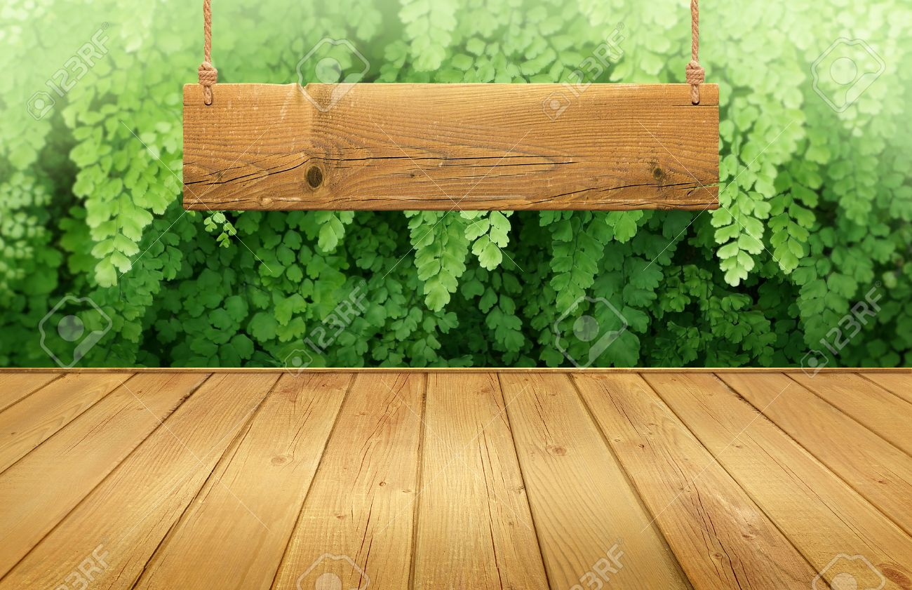 Plain wood table with hipster brick wall background stock photo - Wood Table With Hanging Wooden Sign On Green Leaves Background
