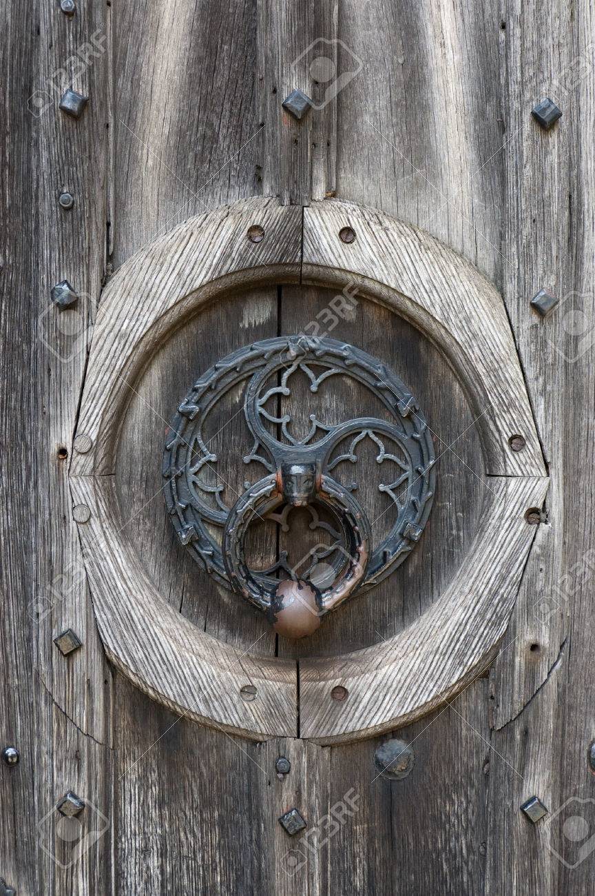 Ornate Door Knocker On A Weathered Wooden Door Stock Photo   1449397