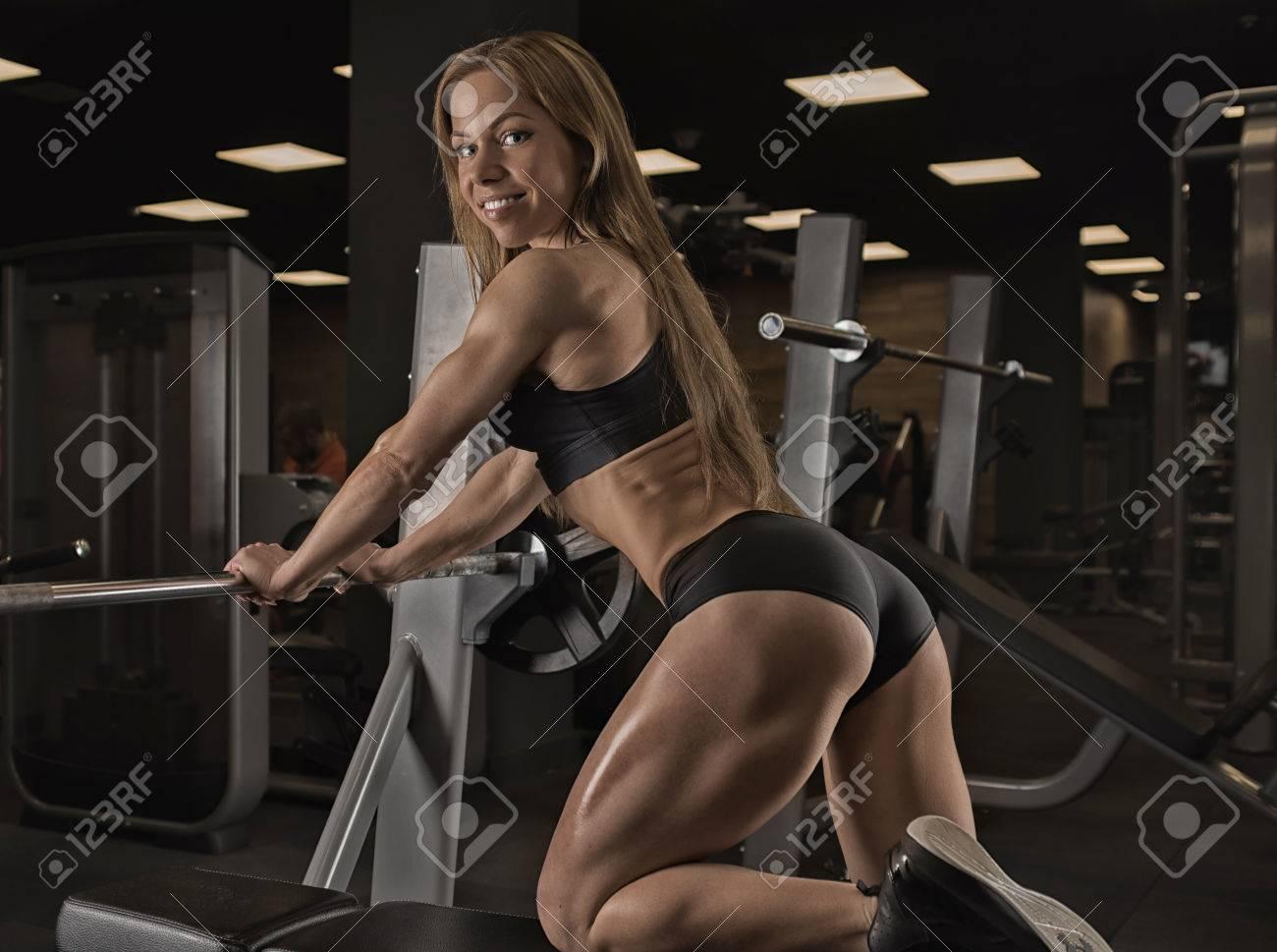 Fille Fitness Photo musclé fille fitness avec un beau sourire posant dans la salle de