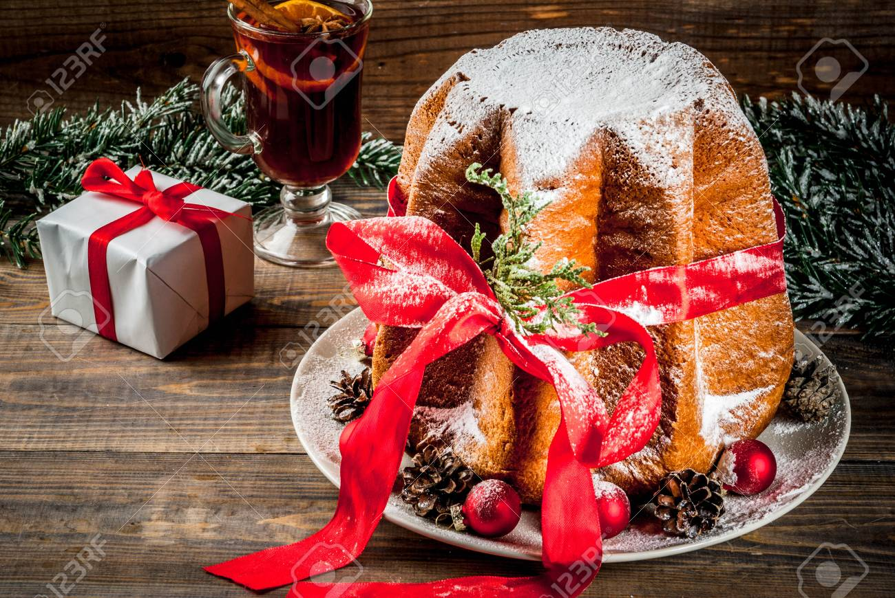 stock photo traditional italian christmas fruit cake panettone pandoro with festive red ribbon and christmas decorations gift box and mulled wine