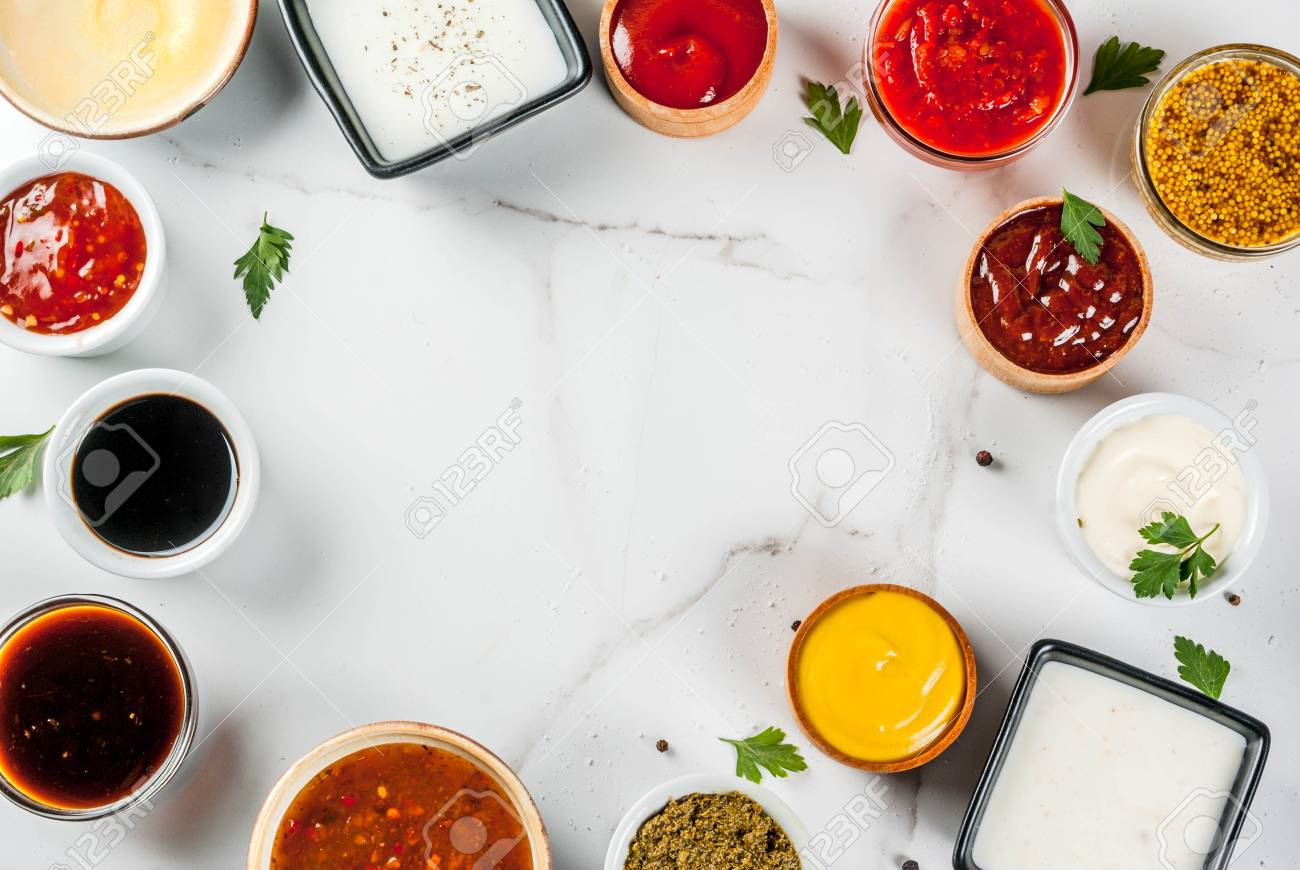 Set of different sauces - ketchup, mayonnaise, barbecue, soy, teriyaki, mustard, grain hills, pesto, adzhika, chutney, tkemali, pomegranate sauce on white marble background. Top view copy space - 94009778
