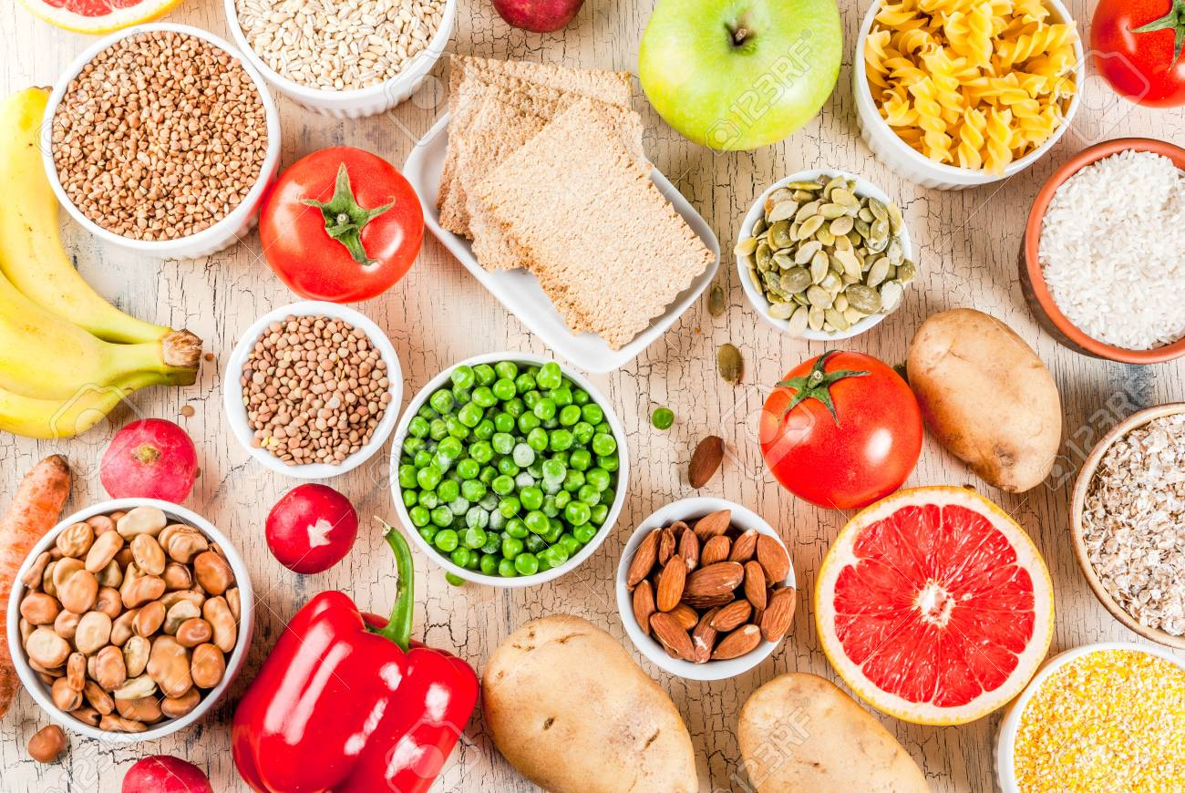 Diet food background concept, healthy carbohydrates (carbs) products - fruits, vegetables, cereals, nuts, beans, light concrete background above - 99509013