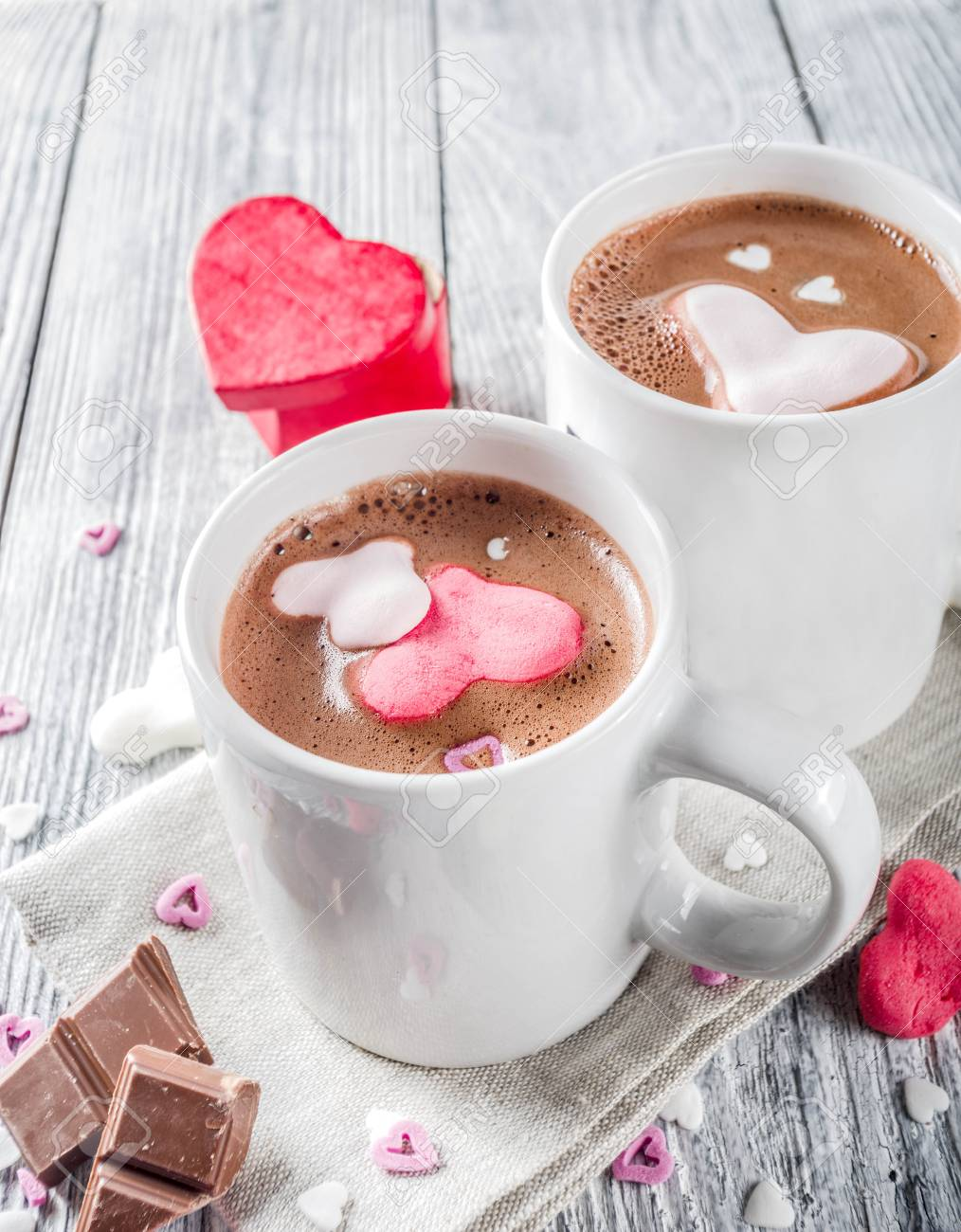 Valentines day treat ideas, two cups hot chocolate drink with marshmallow hearts red pink white color with chocolate pieces, sugar sprinkles, old wooden background copy space top view - 121713602