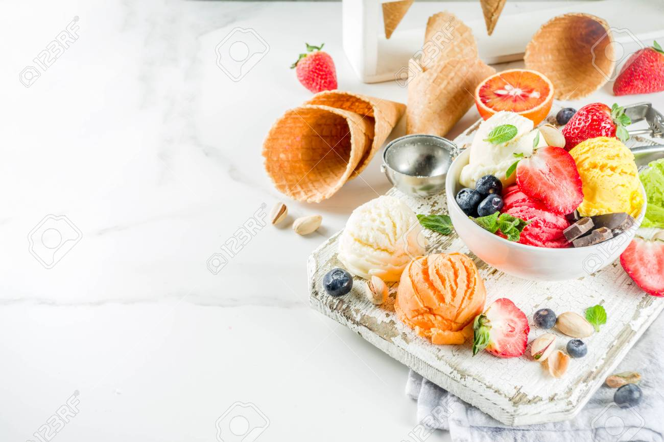 Colorful fruit and berry, nut, chocolate and vanilla ice cream, with waffle ice-cream cones, with fresh fruit and berries, top view copy space white marble background - 121713702