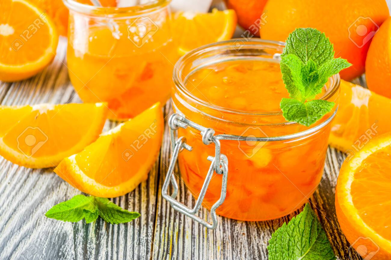 Homemade orange jam, with fresh sliced oranges and mint leaves, white wooden background copy space - 123801577
