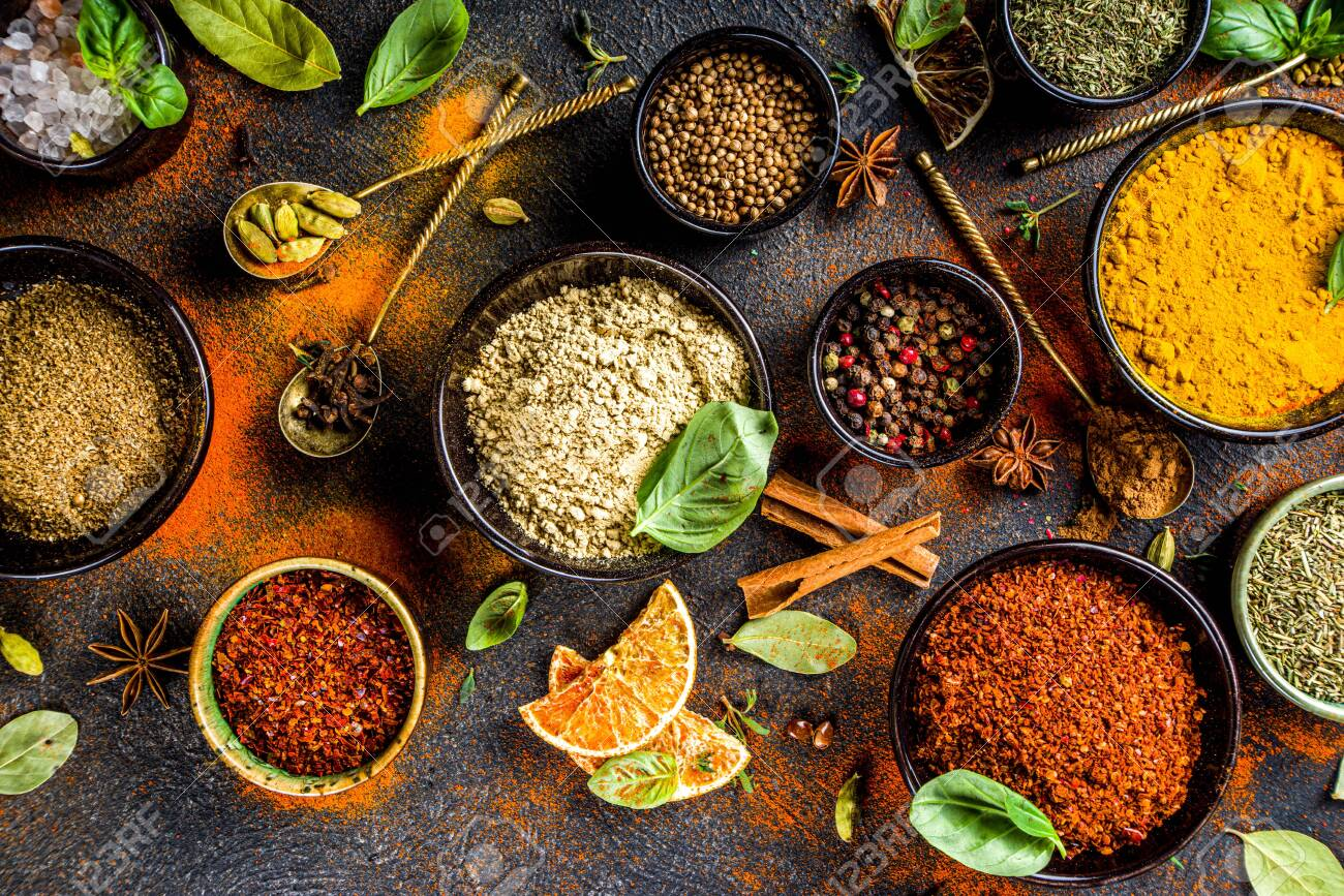 Set of Spices and herbs for cooking. Small bowls with colorful seasonings and spices - basil, pepper, saffron, salt, paprika, turmeric. On black stone table top view copy space - 148088688