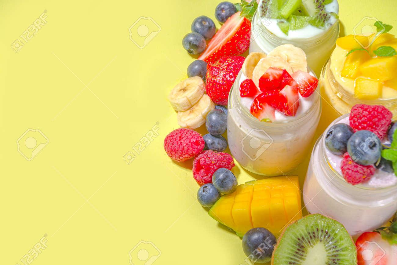 Set of various fruit and berry yogurts in glass jars. Variety healthy Breakfast yoghurt with blueberry, strawberry, mango, kiwi, raspberry, trendy bright yellow background with hard light dark shadows - 165765088