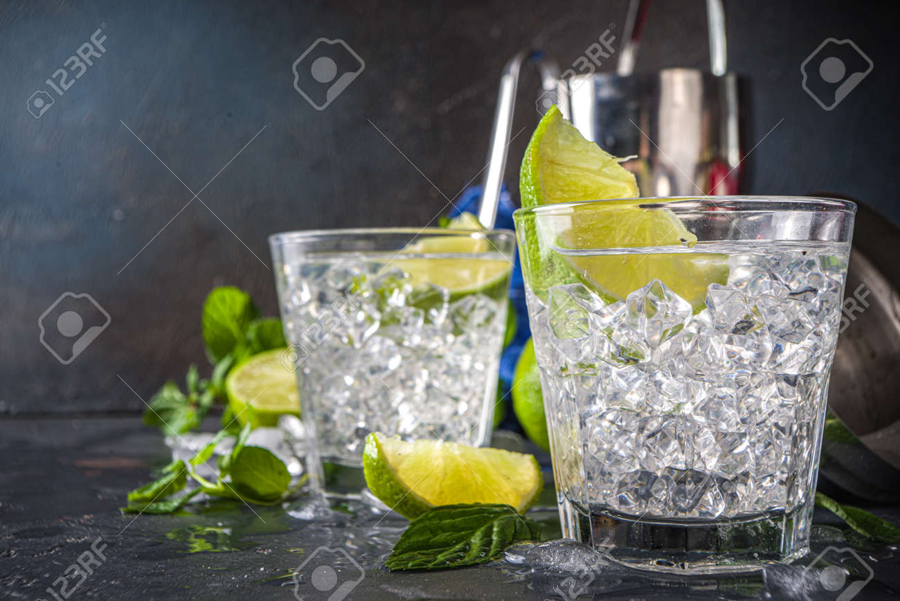 Summer paloma cocktail, vodka lime, mojito or gin tonic with lime wedge and crushed ice in rocks, two cold alcohol beverage glasses on black background copy space - 168951506