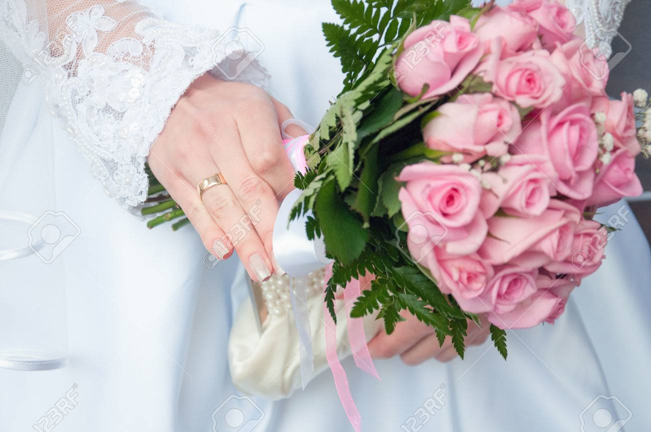 close up of bride hand holding wedding bouquet of roses stock photo