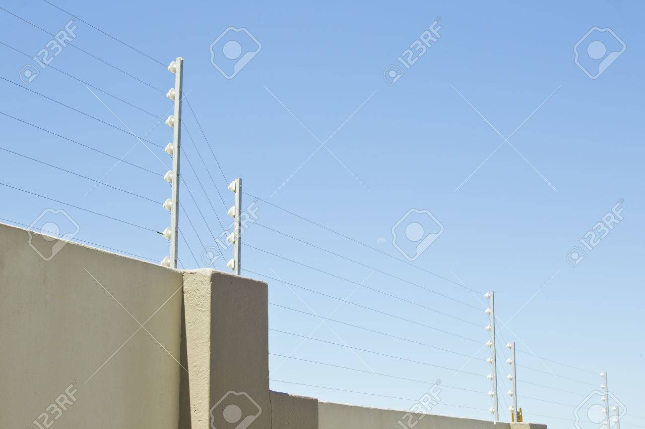 upright poles holding electric fencing cable on a boundary wall Stock Photo - 48864490
