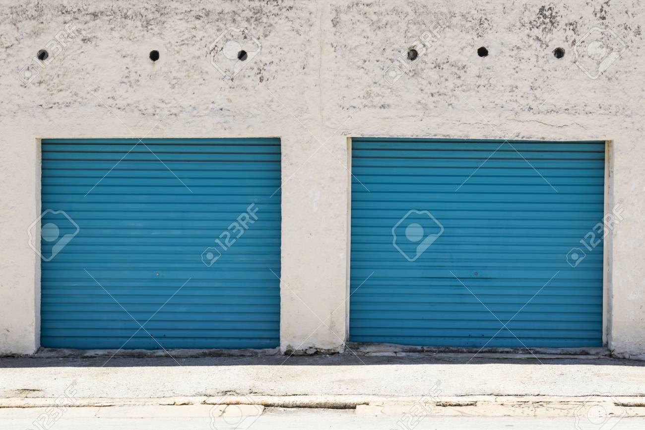 Deux Portes De Garage En Acier Peint En Bleu Avec Peinture écaillée Et Murs Blancs Sales Les Entourant
