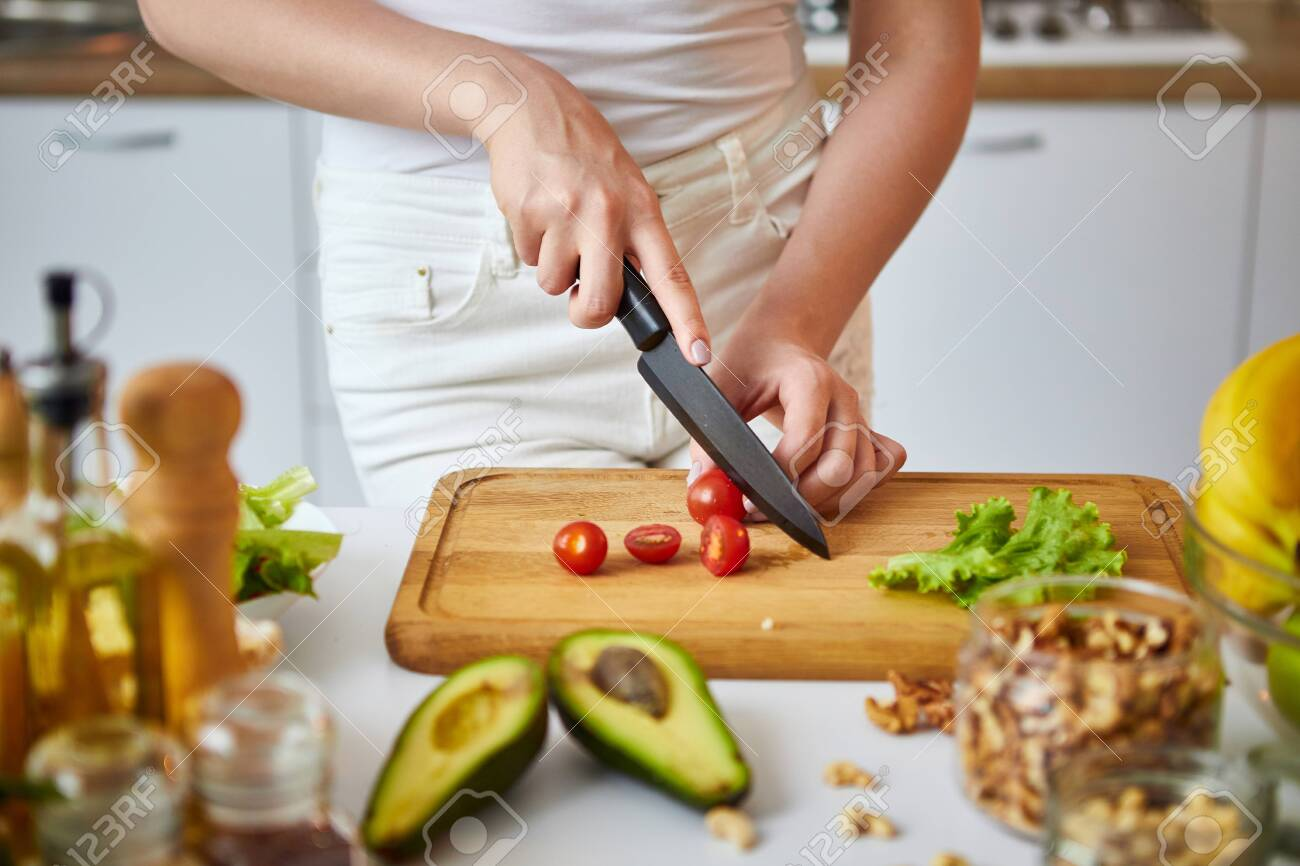Young happy woman cutting tomatoes for making salad in the beautiful kitchen with green fresh ingredients indoors. Healthy food and Dieting concept. Loosing Weight - 129009205