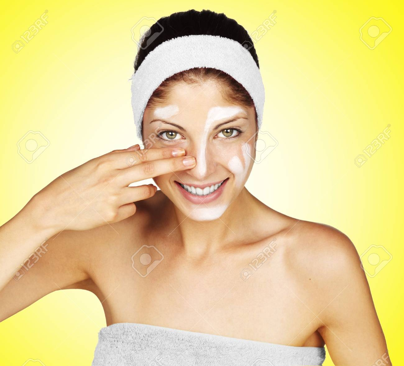 Beautiful young woman applying a creme on her face Stock Photo - 16968842