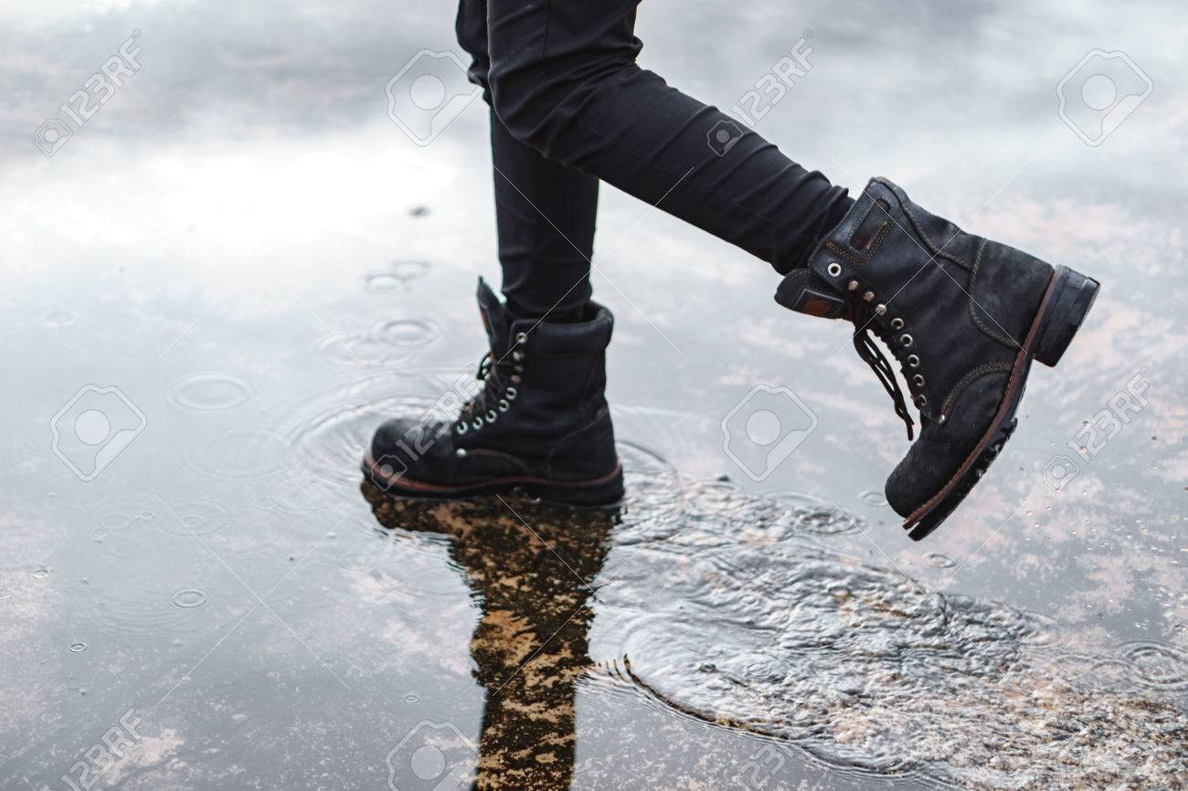 54eacb458 Girl wearing jeans and black combat boots splashing in a puddle after rain  Stock Photo -