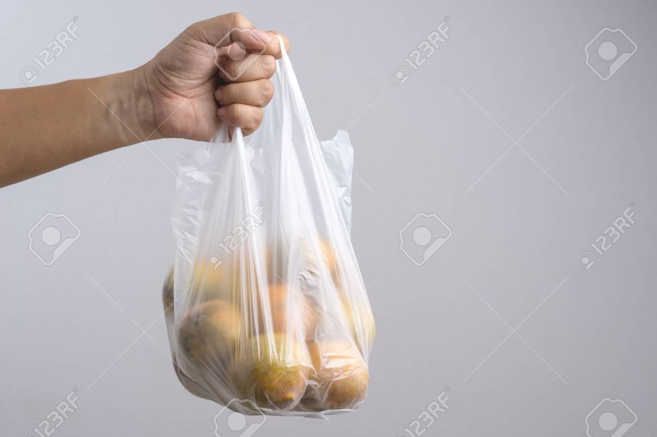 Hand holding plastic bag full of oranges on white background - 74714217