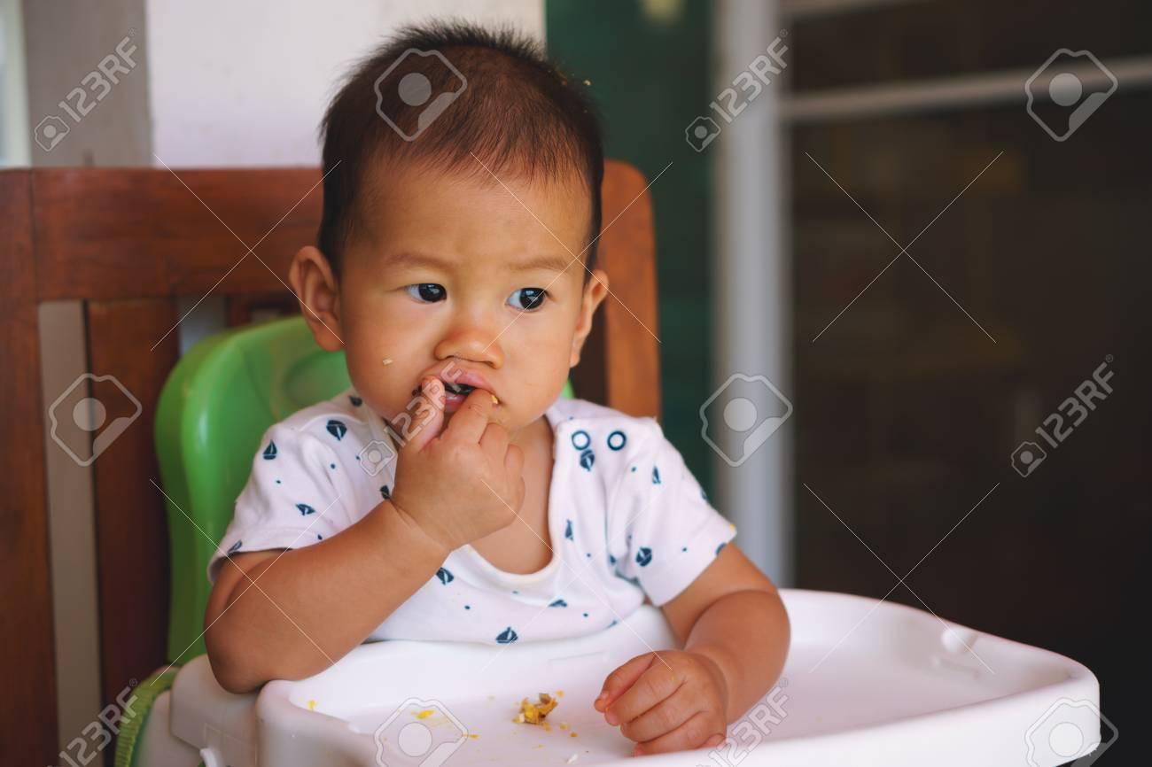 Bébé de 1 an asiatique manger de la nourriture par lui-même
