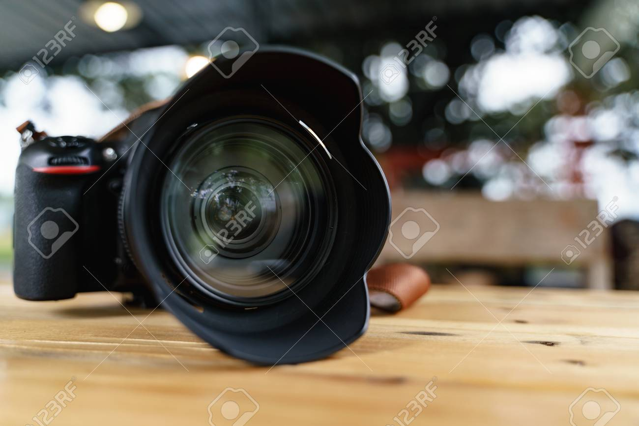 Modern camera lens for professional photography on wooden desk - 117420104