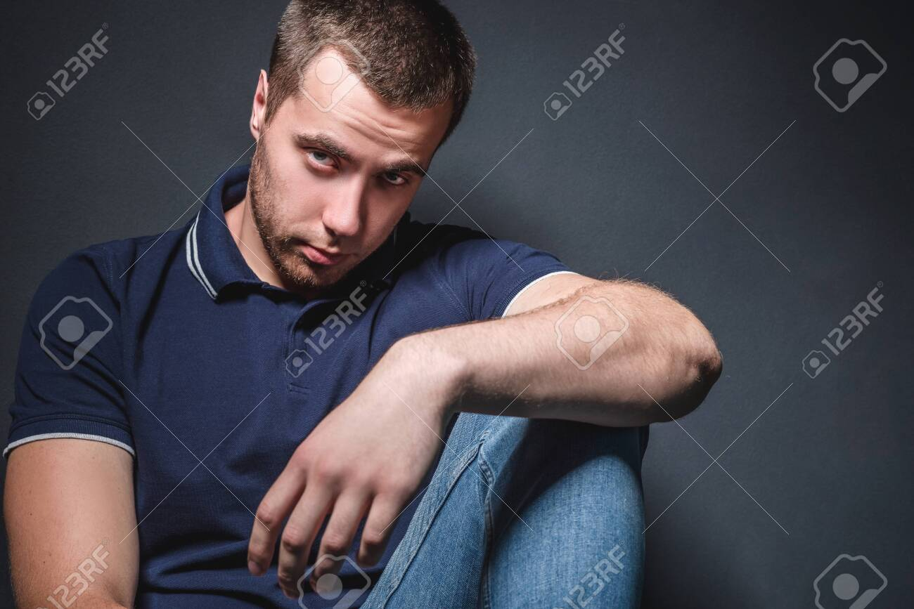 Young attractive man in blue jeans and a polo shirt sits on the floor near the wall in the studio. Youth and attractiveness concept - 154928605