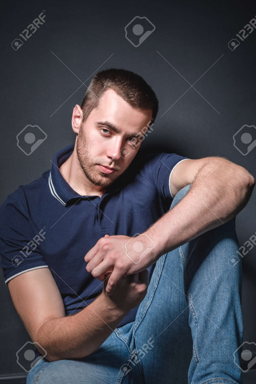 Young attractive man in blue jeans and a polo shirt sits on the floor near the wall in the studio. Youth and attractiveness concept - 155813226