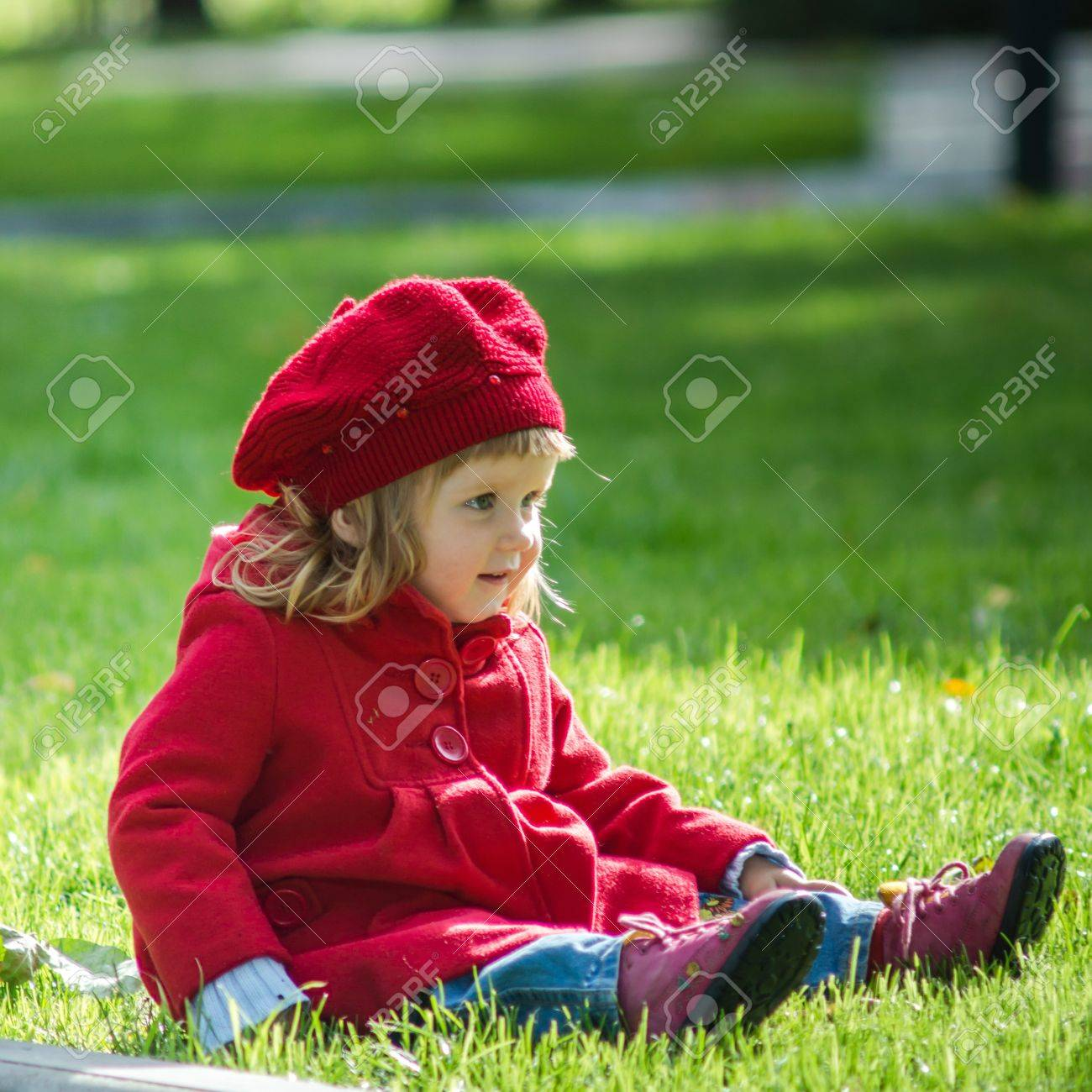 Cute Little Girl Dressing In Red Coat. Autumn Park. Sunny Day