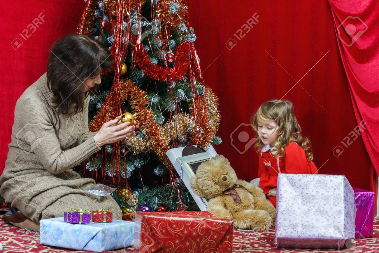Mother with little daughter finding christmas gifts over the tree Stock Photo - 25151145